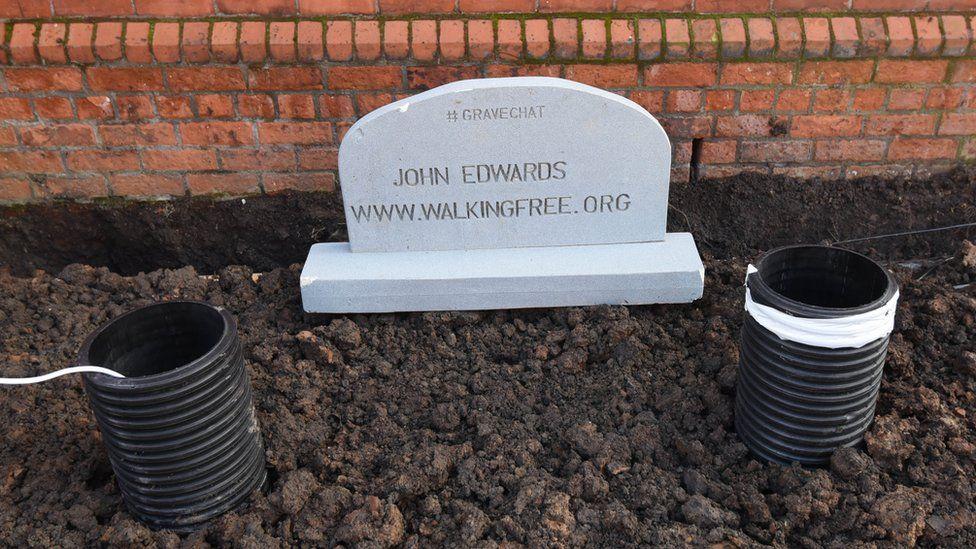 John Edwards under his 'grave'