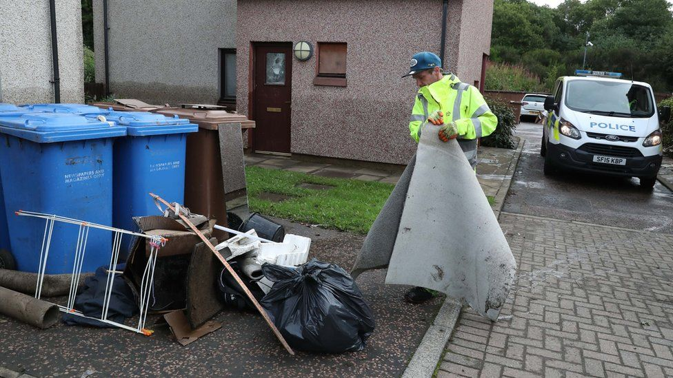 A worker cleaning up after flooding in Pyothall Court in Broxburn, West Lothian.