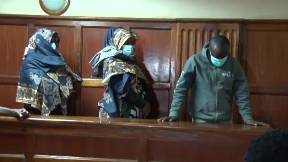The three suspects stand in court