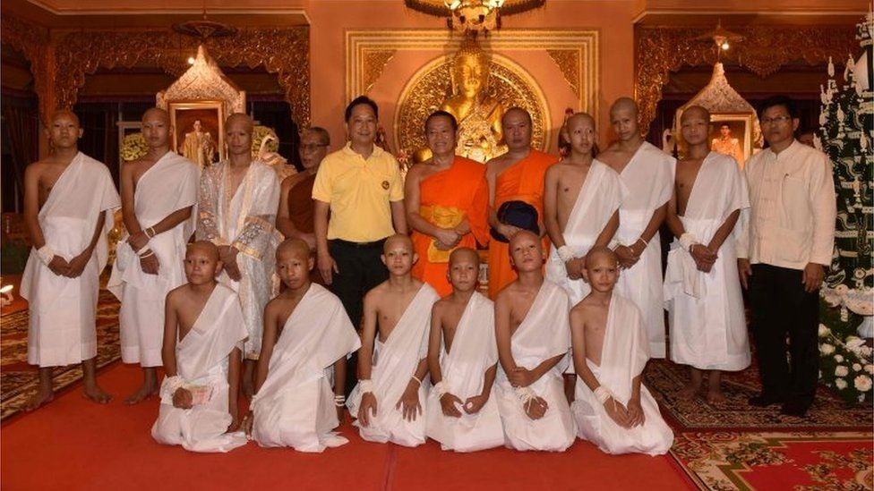 """The rescued 11 Thai boys and members of """"Wild Boars"""" football team together with their coach wearing white robes pose with Buddhist monks at the Phra That Doi Wao Buddhist temple in the Mae Sai district of Chiang Rai province during the religious ordination ceremony on July 24, 2018."""