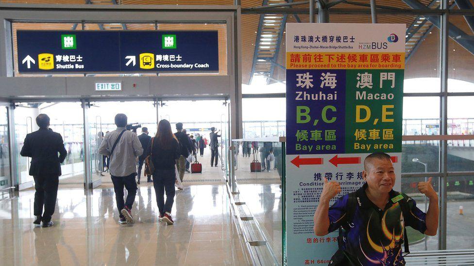A man poses before getting a bus to cross the Hong Kong-Zhuhai-Macau Bridge, in Hong Kong