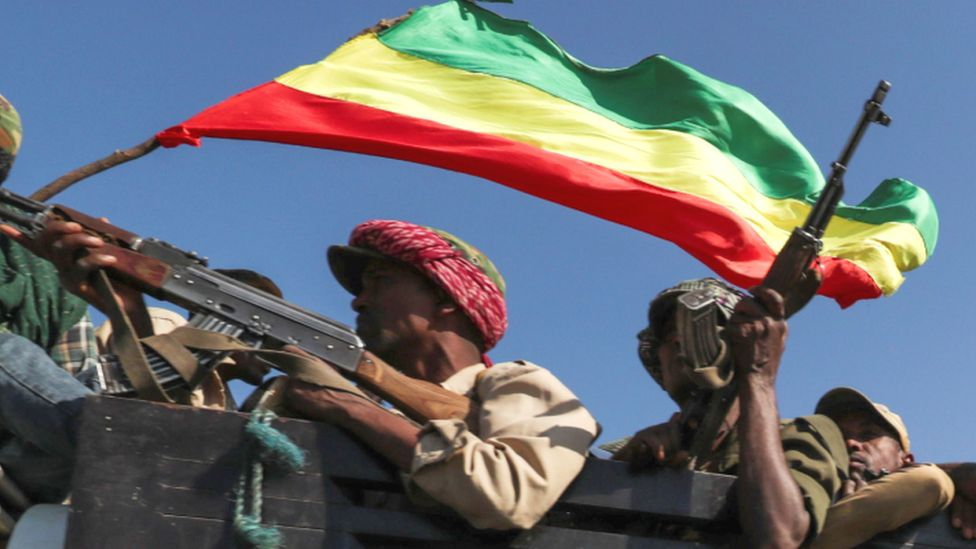 Armed fighters in a truck holding an Ethiopian flag