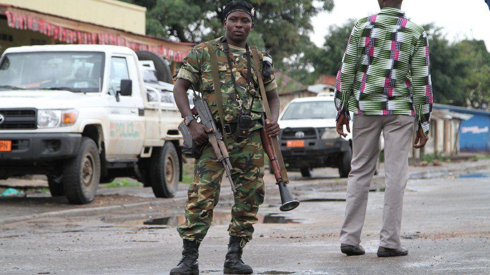 A Burundian soldier with his gun and rocket launcher guard a deserted street in Bujumbura, Burundi (8 Nov. 2015)