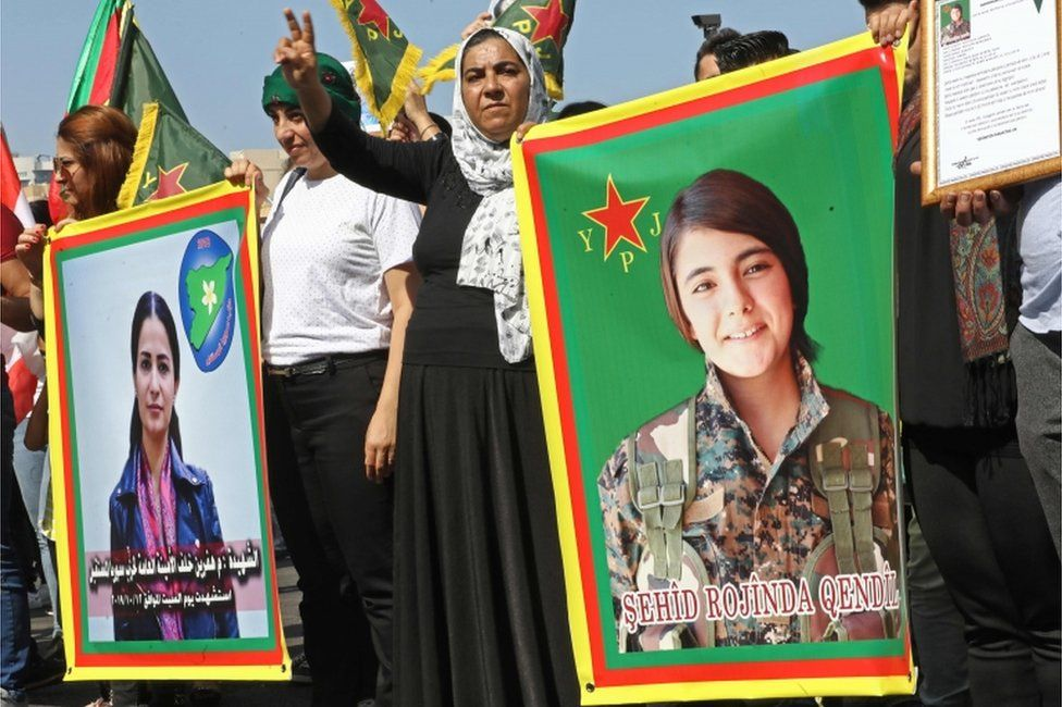 Kurdish protesters wave their national flags and hold photos of Kurdish political leader Hevrin Khalaf (L), who was reportedly killed by Turkish-backed militias, and Sehid Rojinda Qendil, a Kurdish fighter killed in Syria, during a demonstration against the latest Turkish military offensive in north-eastern Syria, in central Beirut's Martyrs Square on October 13, 2019