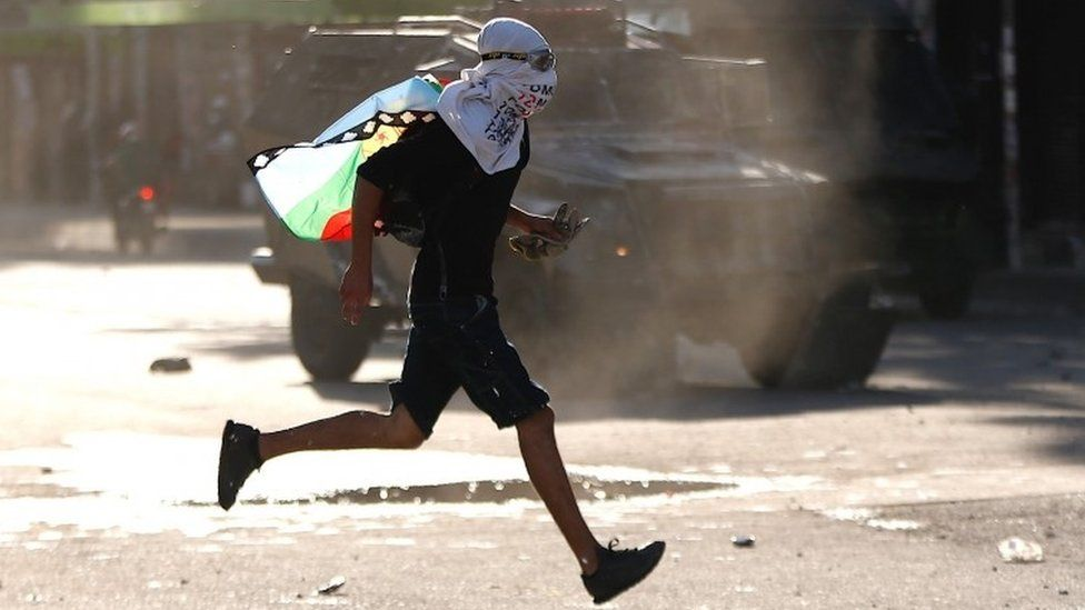 A protester runs during a demonstration in Chile