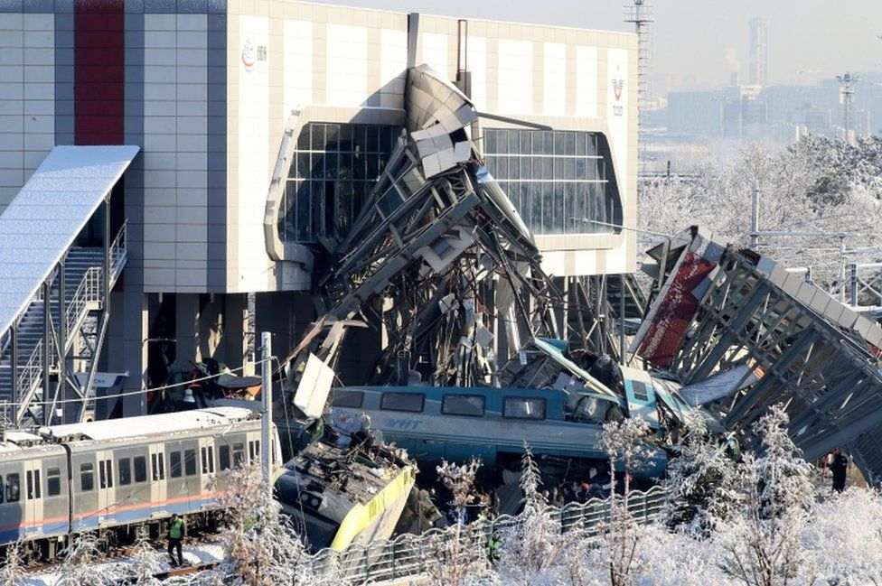 An image shows some train wagons derailed and the metal overpass split in two where the train hit it