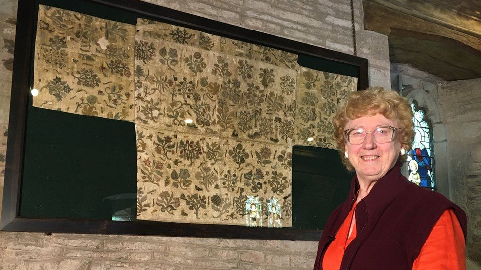 Ruth E. Richardson with the copy of the cloth now hanging on the church wall
