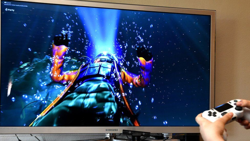 An underwater spacemen floats through the TV screen in front of the player