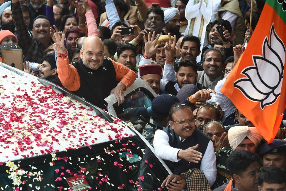 BJP president Amit Shah shows the victory sign to supporters as he arrives to at the party headquarters in Delhi