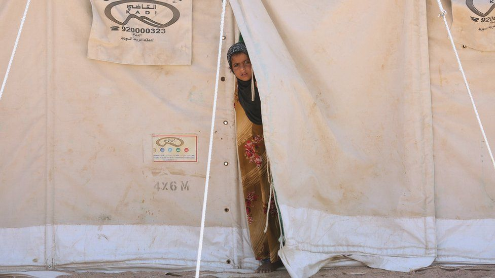 A girl stands in her family's tent at a camp for people displaced by conflict
