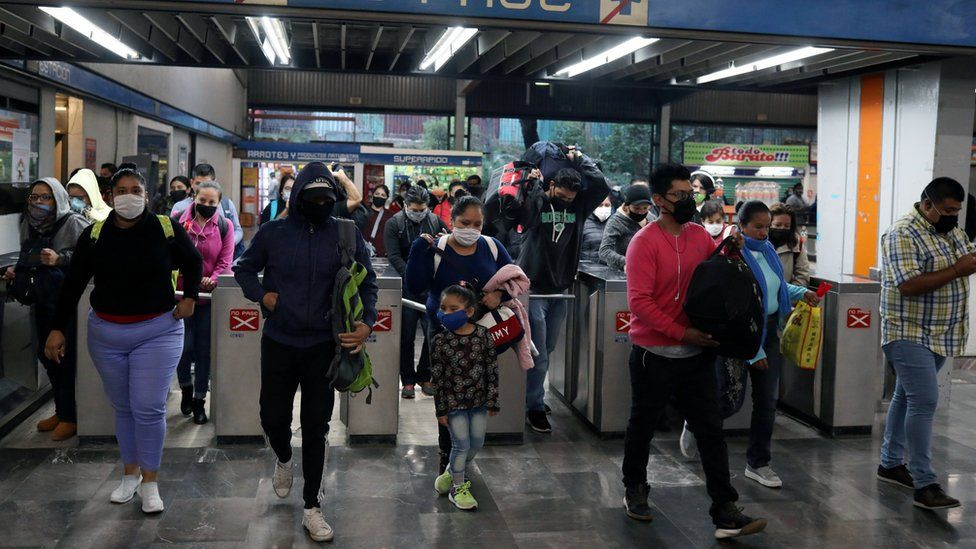 People wearing protective masks walk past the turnstiles inside a subway station in Mexico City