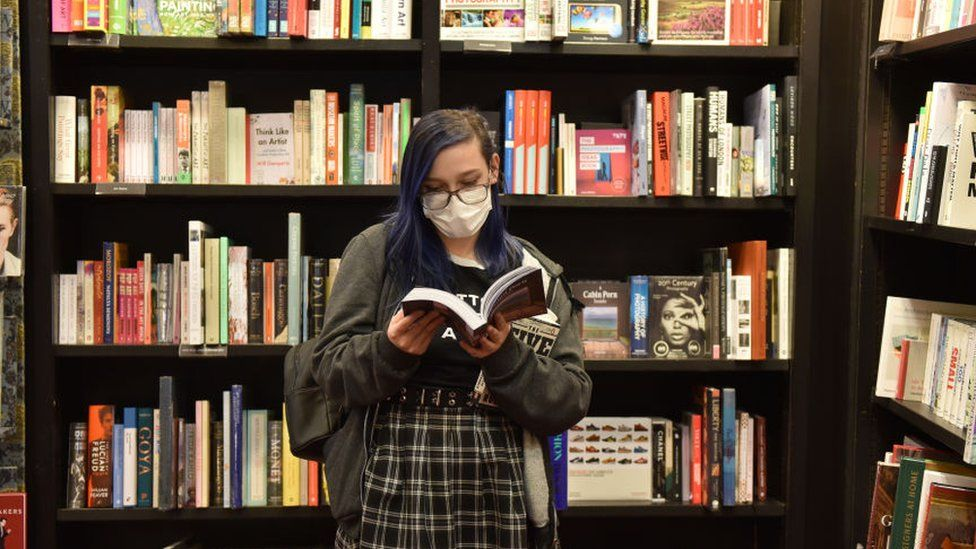Woman in mask reading a book