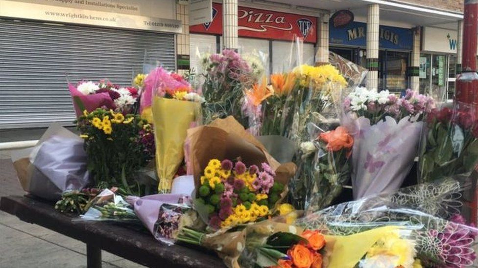 Flowers left near a row of shops in Harlow where a Polish man was attacked.
