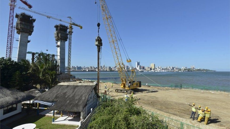 """Construction workers build a new bridge against the skyline of Mozambique""""s capital Maputo"""