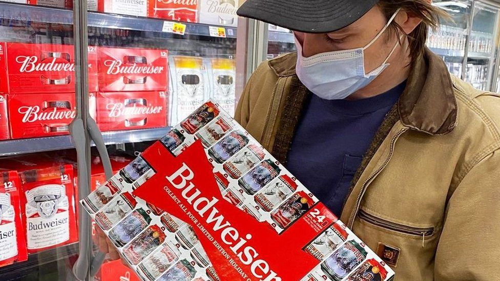 A man holding a case of Budweiser beers in a supermarket