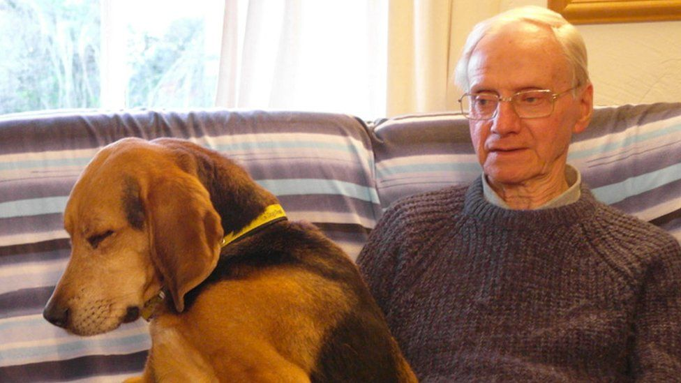 Peter Wrighton, seated, with a dog on his lap