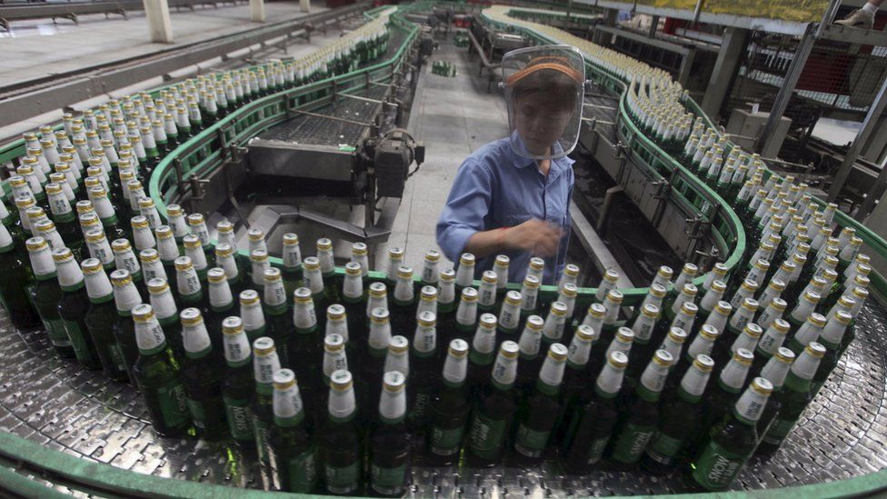 A labourer works at an assembly line in China Resources Snow Breweries Co., Ltd. factory in Lanzhou, 25 August 2010