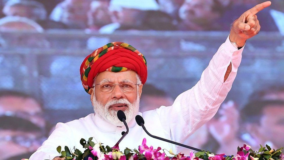 """This handout photograph released by India""""s Press Information Bureau (PIB) on March 4, 2019, shows Indian Prime Minister Narendra Modi addressing a gathering during during the inauguration of various development projects in Jamnagar, in the Indian state of Gujarat."""