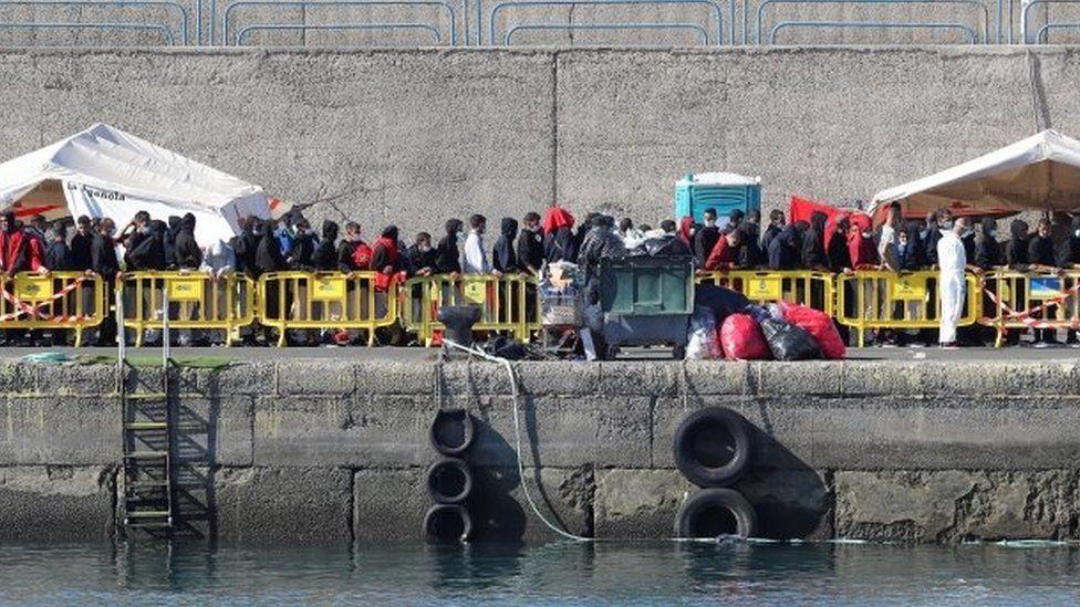 Migrants queue up to receive assistance