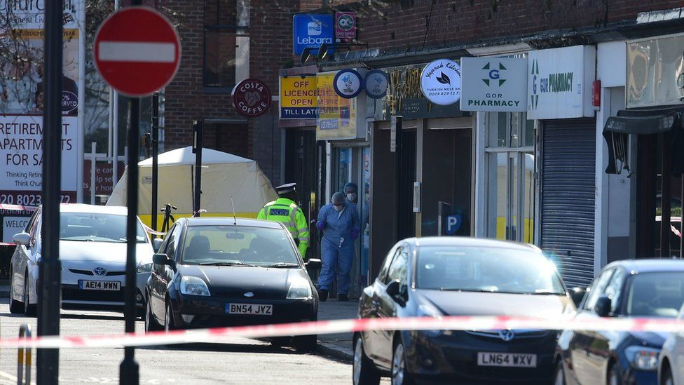 Forensics officers coming out of a shop in Marsh Road, Pinner