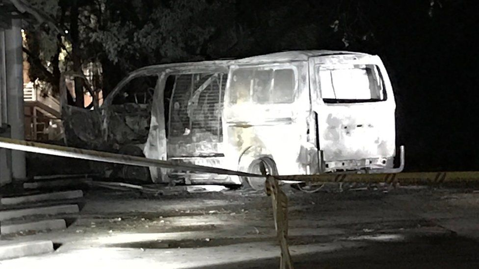 The burnt-out van cordoned off by police tape