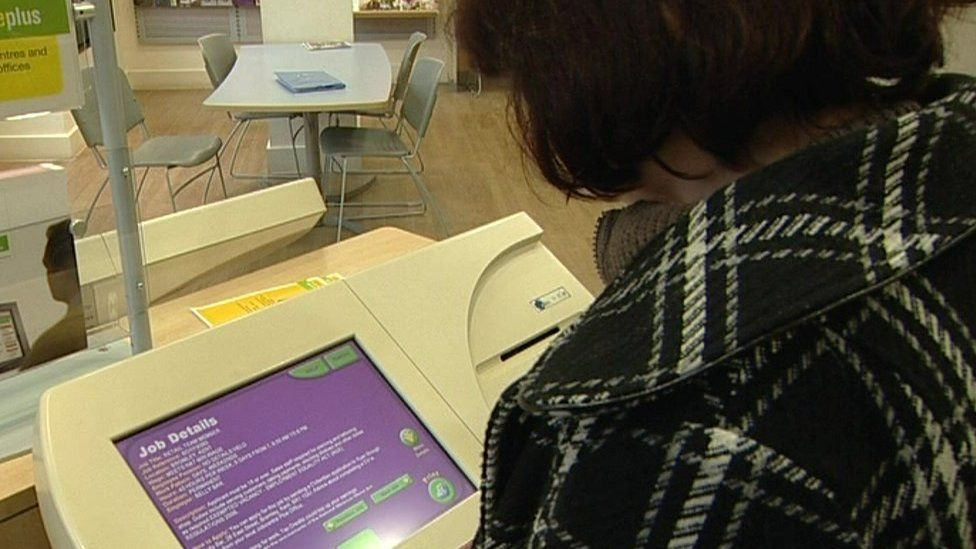 woman looks at jobpoint terminal inside a jobcentre