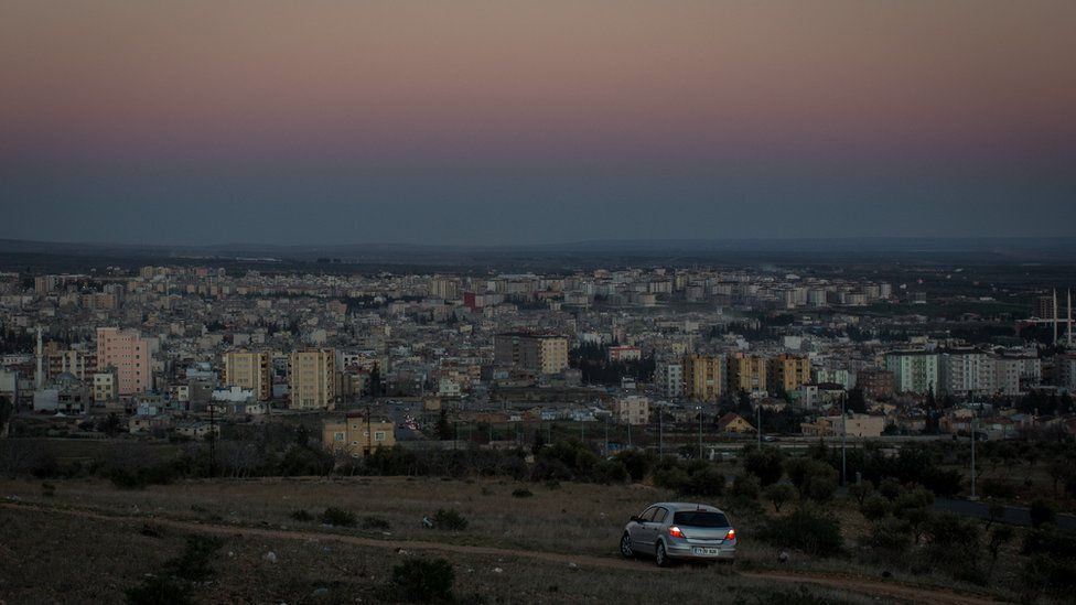 People watch the sunset from their car on a hill overlooking Kilis on March 1, 2016 in Kilis, Turkey
