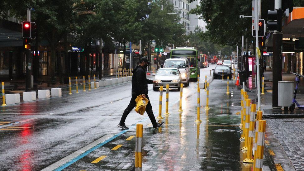 A man in a face mask crosses Queen Street in the early morning rain on February 15, 2021 in Auckland, New Zealand.