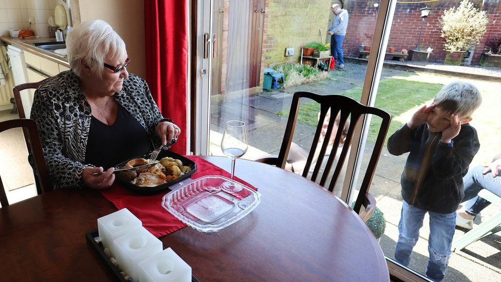 """Zac looks through the window at Vera Barnett after delivering a carvery meal from the Sneyd Arms on Mother""""s Day in Keele, Newcastle-under-Lyme as the spread of the coronavirus disease continues."""
