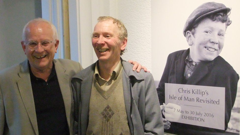 Chris Killip and Keith Callister standing in front of a photo of Keith as a boy