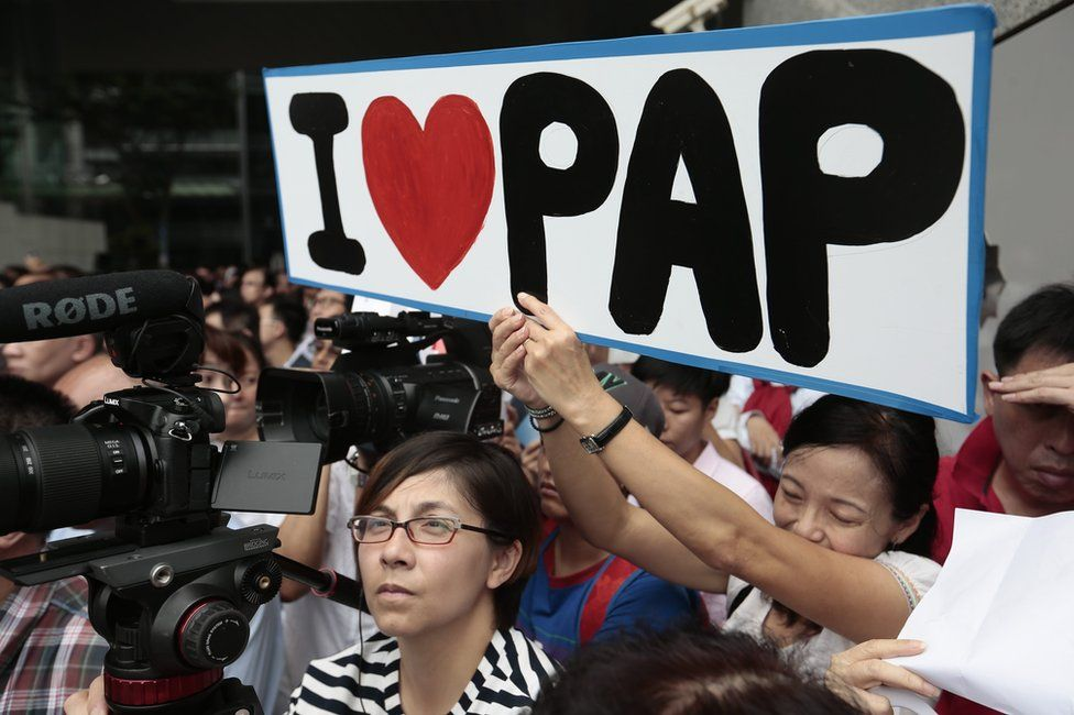 """A supporter of the ruling People""""s Action Party (PAP) holds up a placard during a lunchtime rally in the financial district of Singapore, 8 September 2015"""