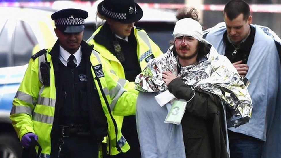 An injured member of the public is escorted from the scene