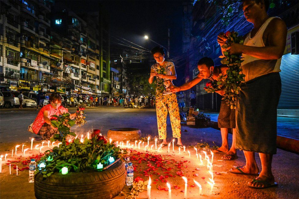 People lay flowers around a circle of candles on a street