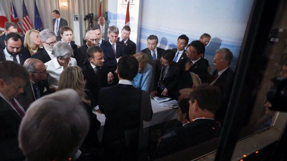 G7 leaders gather in a tight crowd around a narrow table