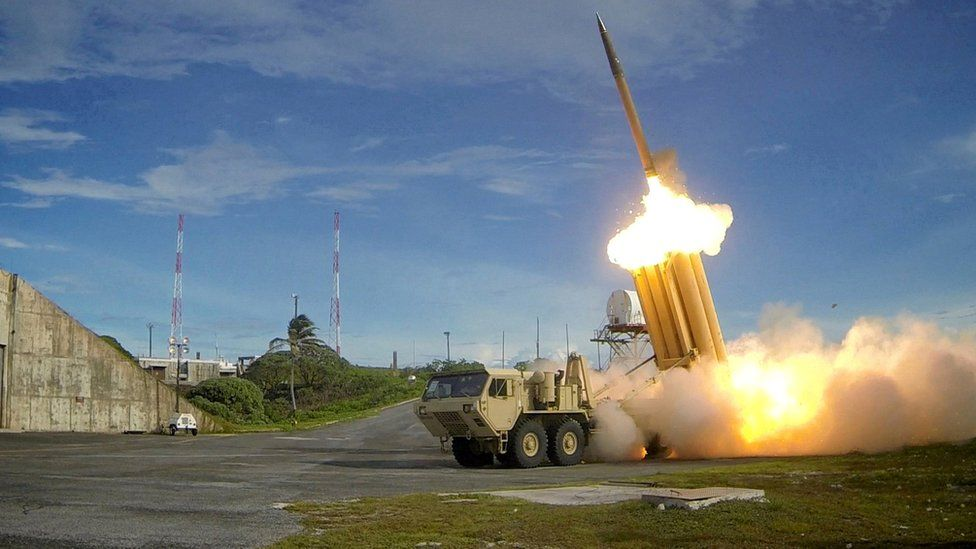 A Thaad launcher, resembling a truck with many large upward- pointing launch tubes, fires an interceptor missile on a testing range in an undated handout photo