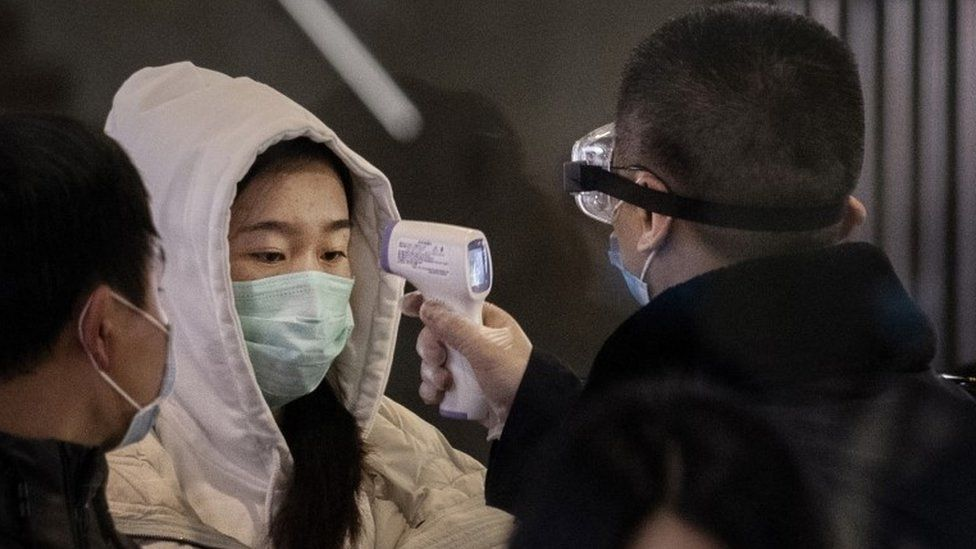 Train passenger being checked for fever