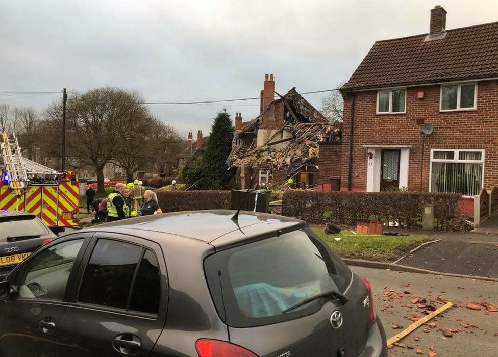 Emergency vehicles in front of a house damaged by an explosion with debris on the floor