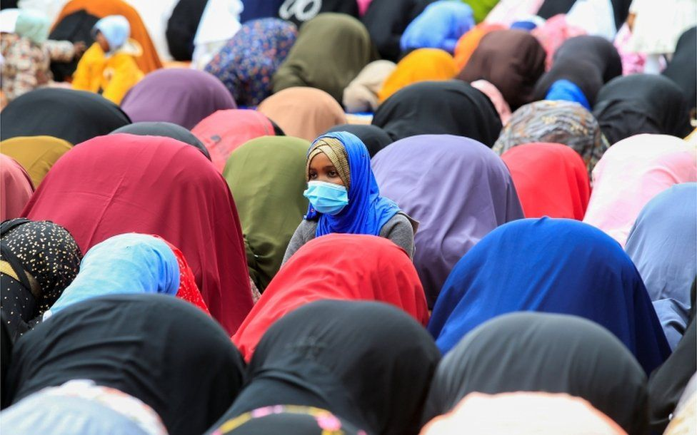 A woman is seen kneeling upright whole others around her are bend forward in prayer.