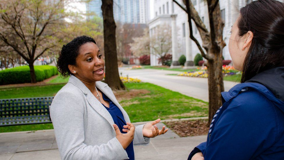 Chandra Farley is shown wearing a blazer and speaking to a woman she is standing across from,