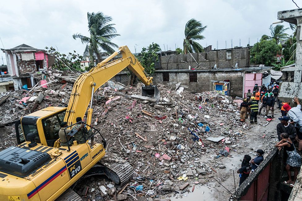 A bulldozer clears the rubble of a collapsed building in Brefet, a neighborhood of Les Cayes, Haiti, on 17 August 2021