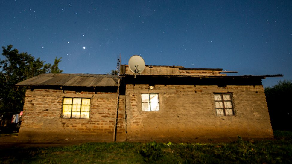 House with satellite dish at night