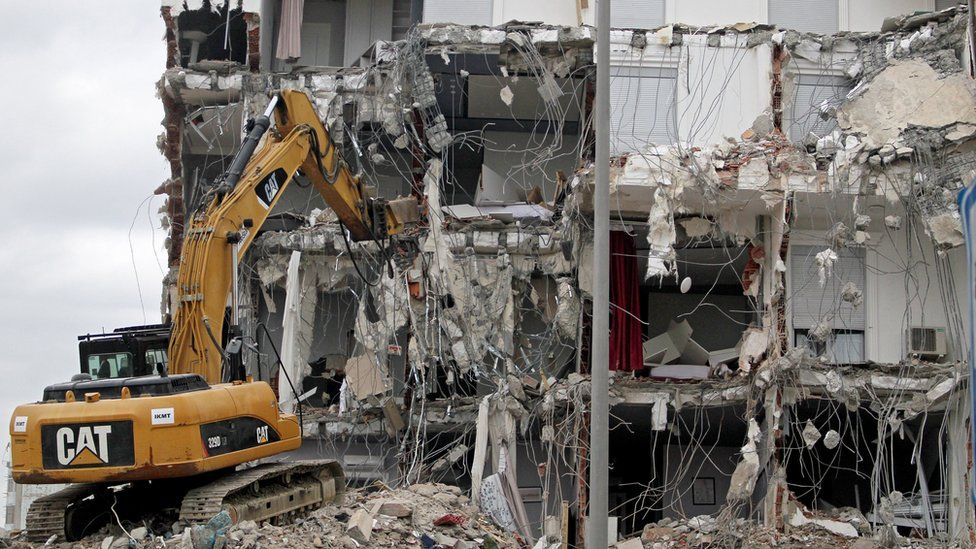 An excavator works at a damaged building in Durres