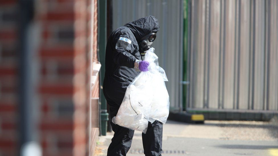 An investigator in a chemical suit removes items in connection with an alleged chemical attack in Salisbury
