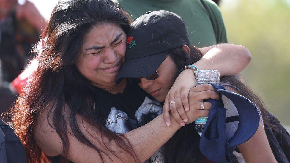 Fernanda Mora (L) an alumna from Deerfield Beach high school and Vallery Cruz a senior at the school hug in front of Marjory Stoneman Douglas High School, 23 February