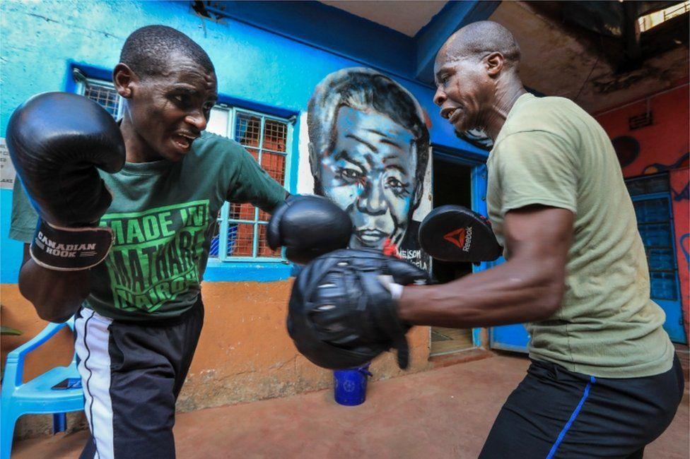 Two men practise boxing.