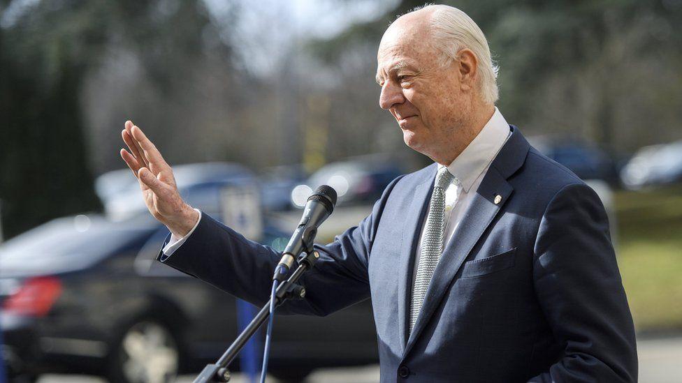 Staffan de Mistura, seen holding a hand up, palm open, standing before a microphone at a press event