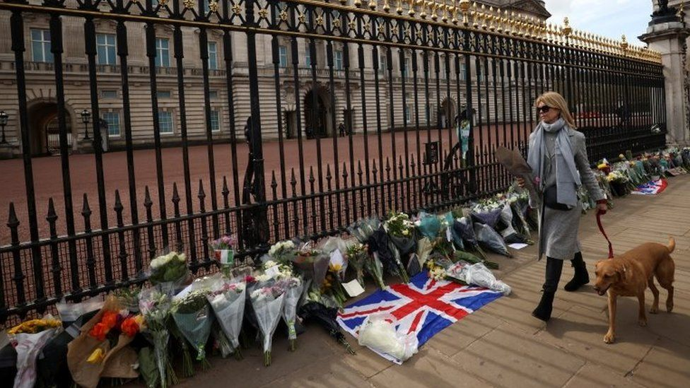 A mourner brings flowers to Buckingham Palace
