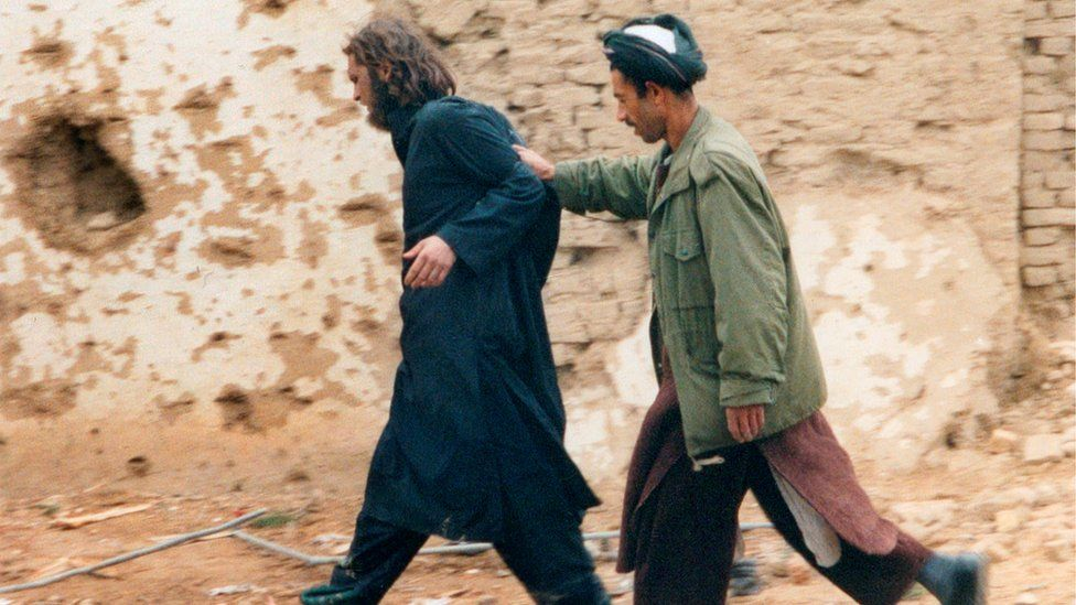 John Walker Lindh, left, photographed as he is captured by Northern Alliance Afghan forces in 2001