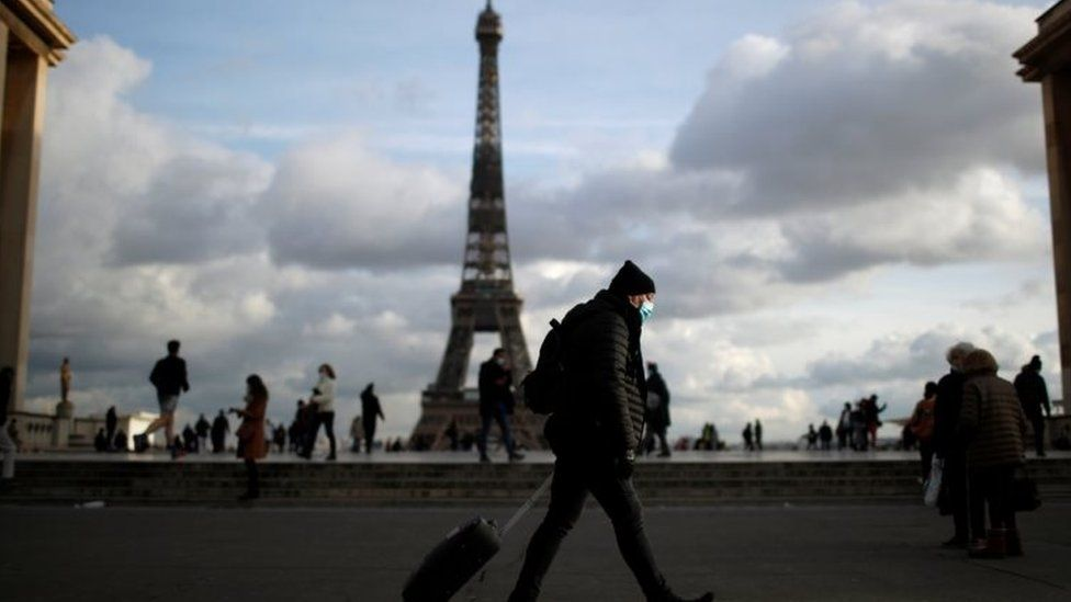 A man wearing a protective face mask walks at Trocadero square near the Eiffel Tower in Paris