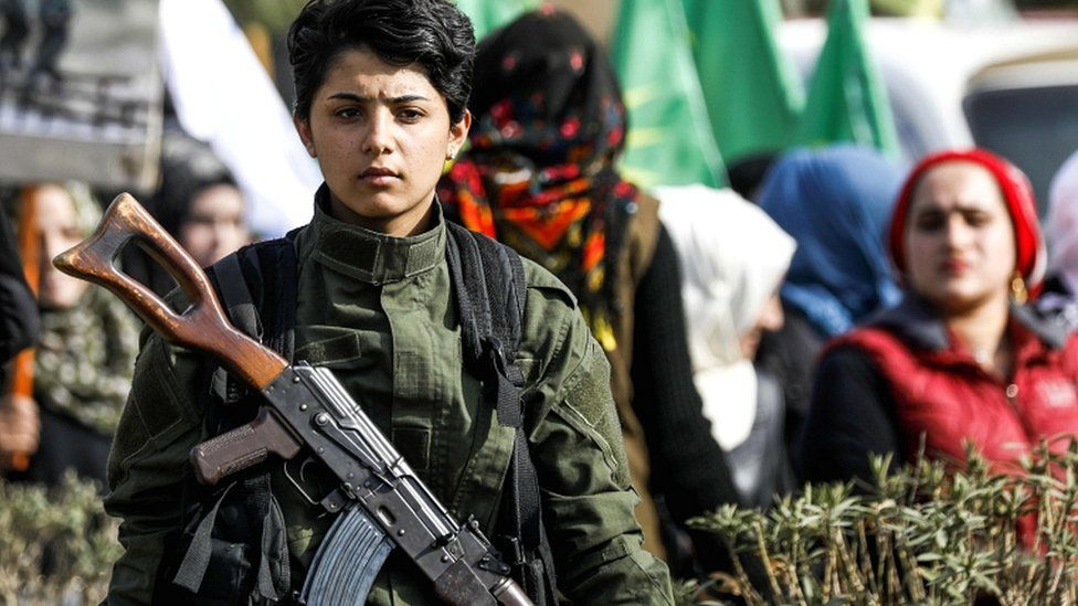 A Syrian Kurdish woman fighter stands as others march past during a demonstration in the north-eastern Syrian city of Qamishli as they mark the International Day for the Elimination of Violence against Women